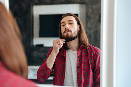 Handsome young man looking at the mirror and combing his beard at home Stock Photo