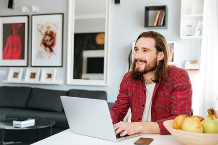 tabla de surf: Cheerful bearded young man sitting at the table using laptop at home