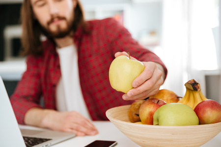 Closeup of bearded young man eating fruits and using laptop at home