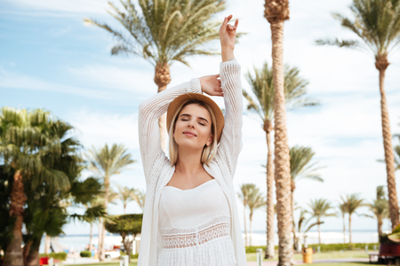 Smiling relaxed young woman standing with raised hands and closed eyes on summer resort