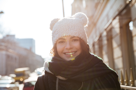 Photo of pretty young woman walking on the street wearing hat while looking at camera. Stok Fotoğraf