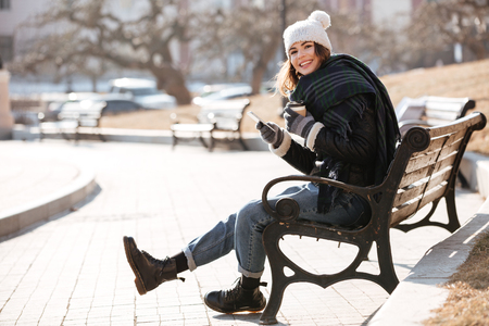 Smiling lovely young woman with cup of coffee using mobile phone on the bench in park
