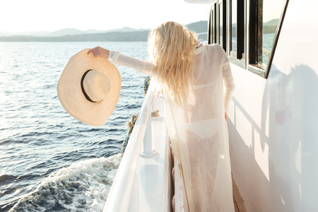Back view photo of young attractive woman holding hat posing on the yacht Stock Photo