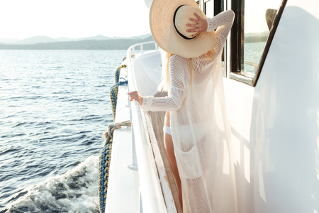 Back view picture of young amazing woman wearing hat posing on the yacht