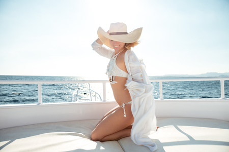 Image of young amazing woman wearing hat sitting on the yacht