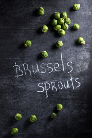 Top view photo of a lot of brussels sprouts over dark background.