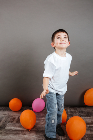Joyful little boy playing with colorful balloons