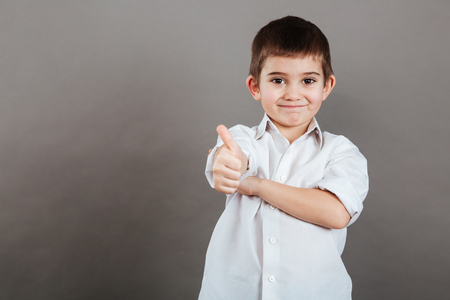Happy little boy standing and showing thumbs up over grey background