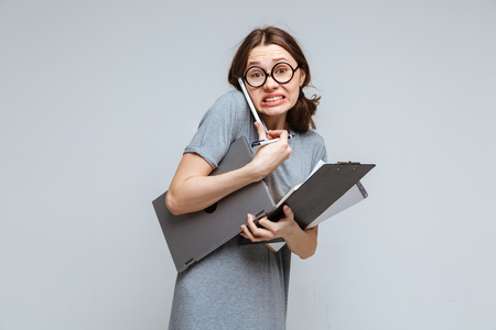 Guilty female nerd in funny eyeglsses which talking on phone and holding laptop, clipboard and notebook Stock Photo