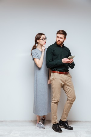 Vertical image of Female nerd in funny eyeglasses standing near the bearded man which recounts money