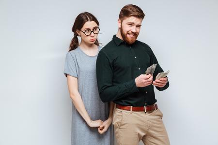 Upset Female nerd standing near the bearded man which recounts the money