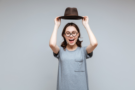 Laughing Female nerd in eyeglasses holding overhead her hat and looking at camera