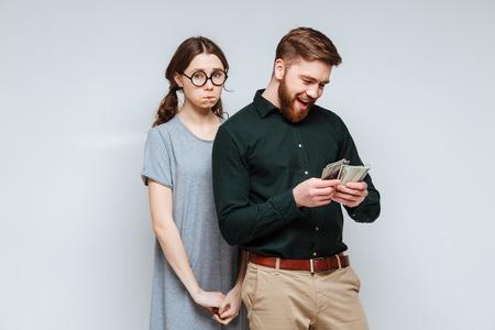 Upset Female nerd in funny eyeglasses standing near the bearded man which recounts the money