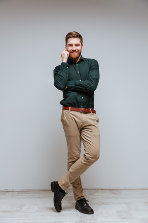 Vertical image of Smiling Bearded man in shirt talking on phone and looking at camera Stock Photo