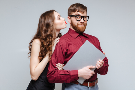 Woman kissing of Male nerd in eyeglasses which holding laptop. Isolated gray background