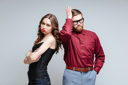 Displeased woman with male nerd in unny clothes and eyeglasses