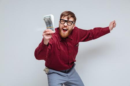 手のお金をそんな幸せな男性のおたく。孤立した灰色の背景 写真素材
