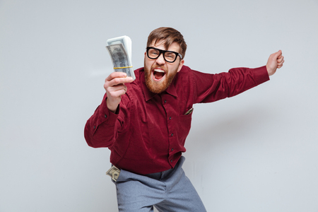 So Happy Male nerd with money in hand. Isolated gray background Stock Photo - 74567006