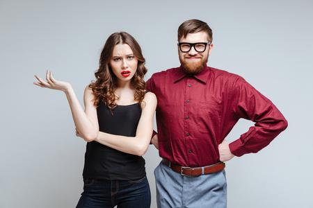 Verrast vrouw met lachende mannelijke nerd die armen in de heup houdt Stockfoto