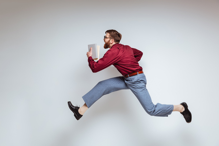 Male nerd running with books in studio. Isolated gray background Reklamní fotografie