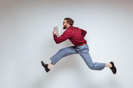 Mannelijke nerd die met boeken in studio loopt. Geïsoleerde grijze achtergrond Stockfoto