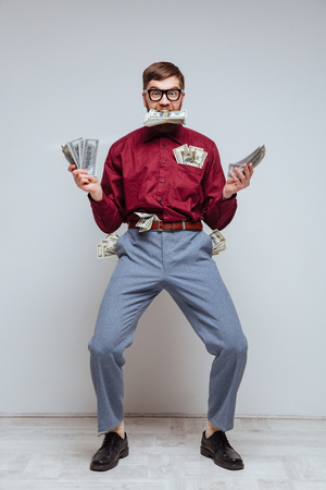 Vertical image of Happy Male nerd with money in hands and in pockets