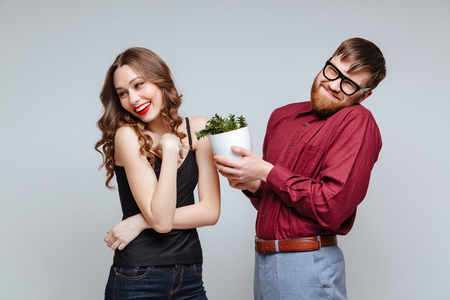 Shy Male nerd presents the plant for Shy girl. Isolated gray background
