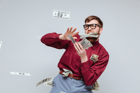 Gelukkig Mannelijk nerd spelen met geld in de studio. Geïsoleerdeg grijze achtergrond Stockfoto