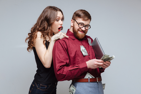 Shocked Girl from back of Male nerd which recounts the money Stock Photo