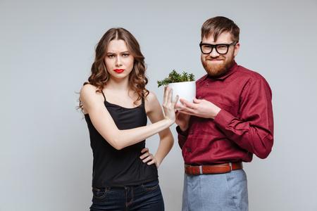 Mannelijke nerd presenteert de plant voor ontevreden meisje. Geïsoleerdeg grijze achtergrond