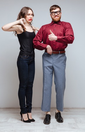 Vertical image of Displeased Woman which showing thumb down and holding hand of Male nerd which showing thumb up Stock Photo
