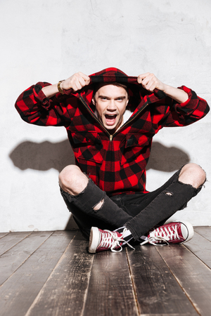 Vertical image of Screaming Hipster in shirt sitting on the floor and holding his shirt