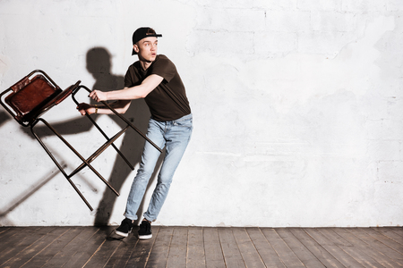 rudeness: Hipster in snap back holding chair in hands and