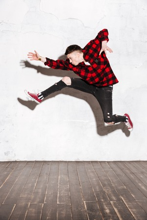 Vertical image of Young Hipster jumping in studio and looking away. Full length portrait Stock Photo