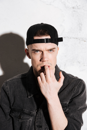 supercilious: Vertical image of hipster in snap back posing near the wall and holding middle finger in the mouth