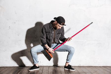 antisocial: Full length image of Hipster in snap back playing on mop