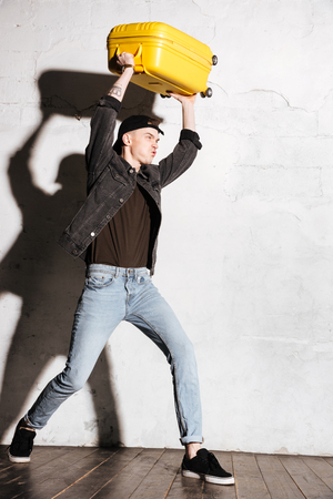 supercilious: Vertical image of Hipster in snap back holding suitcase overhead. Side view