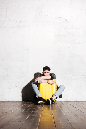 supercilious: Vertical image of Hipster in snap back sitting on the floor and hugging suitcase