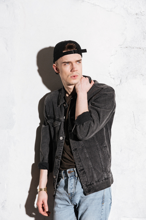 supercilious: Vertical image of hipster in snap back and jeans shirt which looking away and posing near the gray wall