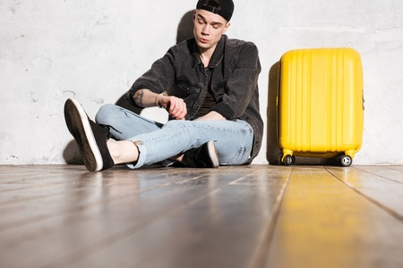 supercilious: Hipster in snap back sitting on the floor near the wall with suitcase and looking at wristwatch