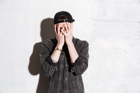 Hipster in snap back covers his face over gray background