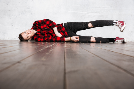 supercilious: Hipster in shirt lying on the floor and looking at camera