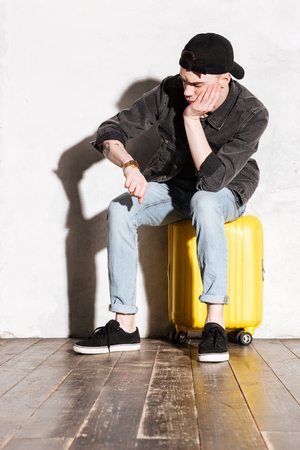 supercilious: Vertical image of Hipster in snap back sitting on suitcase, waiting and looking at wristwatch