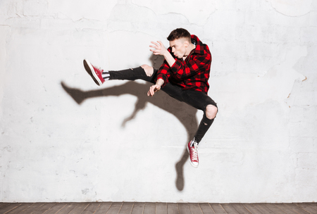 supercilious: Hipster in red shirt jumping in studio. Full length portrait. Side view Stock Photo