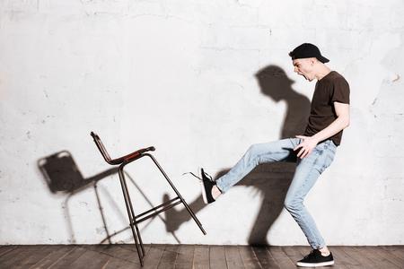 椅子を蹴って戻ってスナップで流行に敏感。完全な長さの肖像画。横から見た図 写真素材
