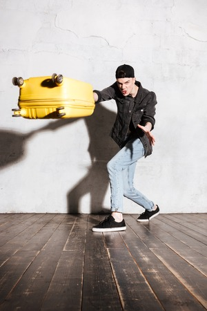 supercilious: Vertical image of Hipster in snap back throwing suitcase at camera Stock Photo