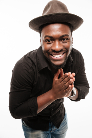 Photo of happy young african man dressed in shirt isolated over white background. Looking at camera. Stock Photo