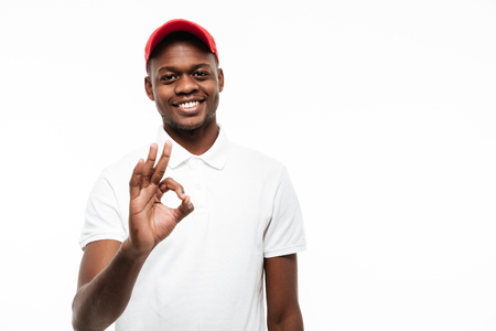 Picture of cheerful young african man wearing cap isolated over white background make okay gesture. Looking at camera. Stock Photo