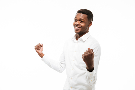 Image of happy young african man dressed in shirt isolated over white background. Make winner gesture.