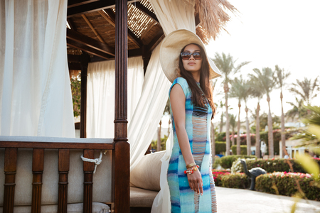 beachwear 및 alcove 근처에 포즈를 취하 고 멀리 찾고 sunglases에서 갈색 머리 여자의 측면보기